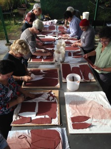 Workshop participants cut leaf shapes out of thin slabs of pre rolled terracotta paper clay